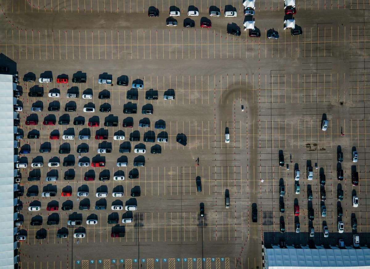 People wait in their cars for a vaccination against COVID-19 at a drive-thru vaccination site set up by the city and United Memorial Medical Center, Thursday, Jan. 28, 2021, at Delmar Stadium in Houston. The vaccinations, the Moderna vaccine, are available by appointment only.