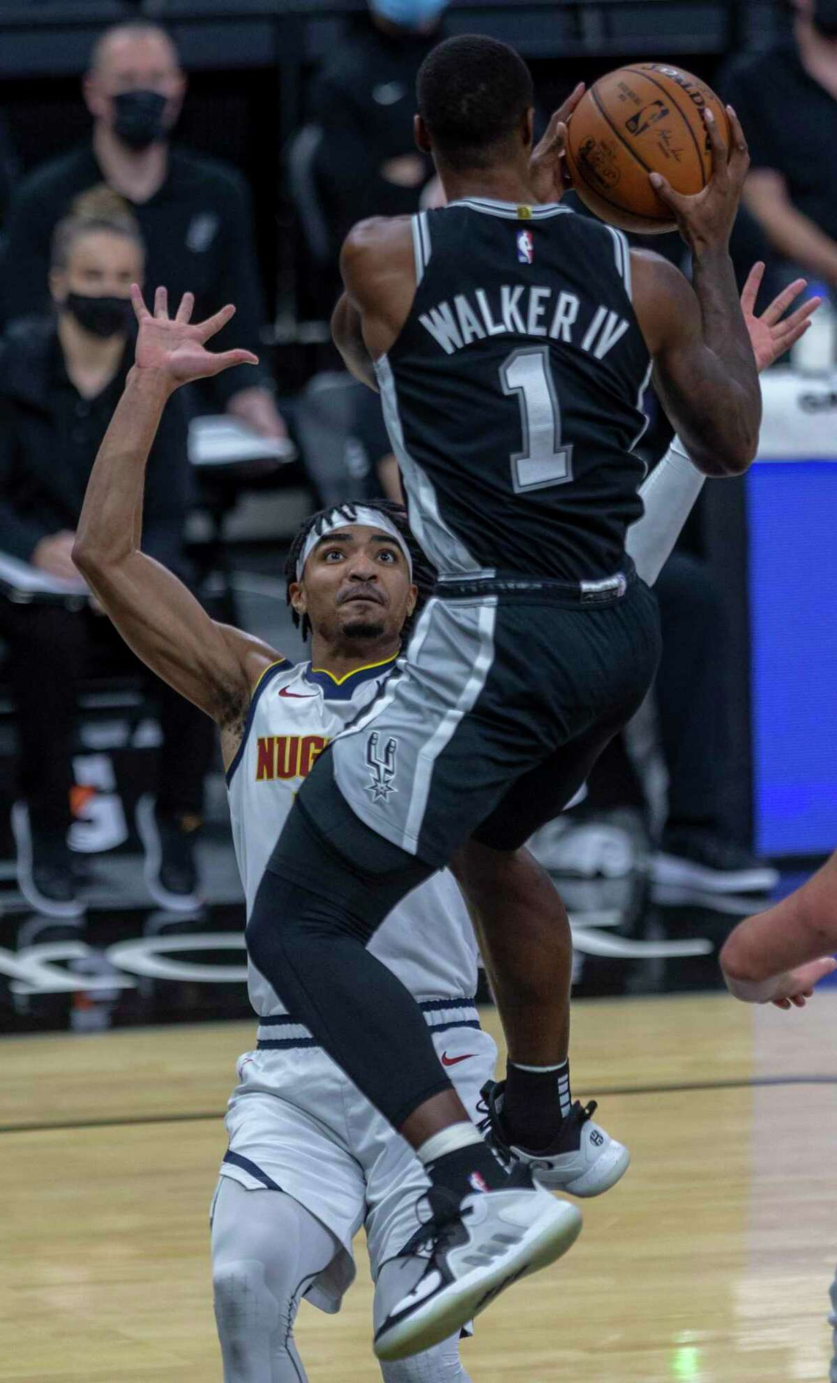 Spurs guard Lonnie Walker IV looks Friday night, Jan. 29, 2021, at the AT&T Center for an out from under the net while Denver guard Gary Harris defends him during the first half of San Antonio's game against Denver.