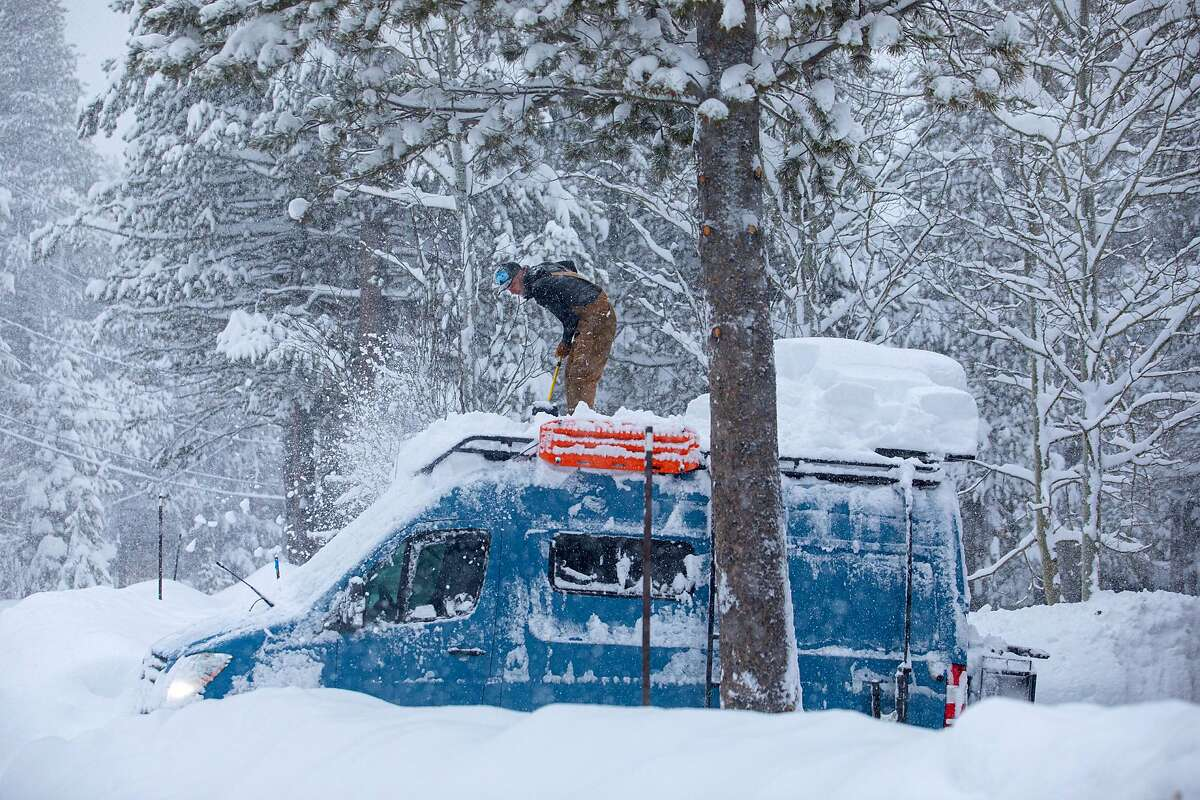 A man digs out his truck during a heavy snowfall in Tahoe City, Calif. during a heavy winter storm on Jan. 28, 2021.