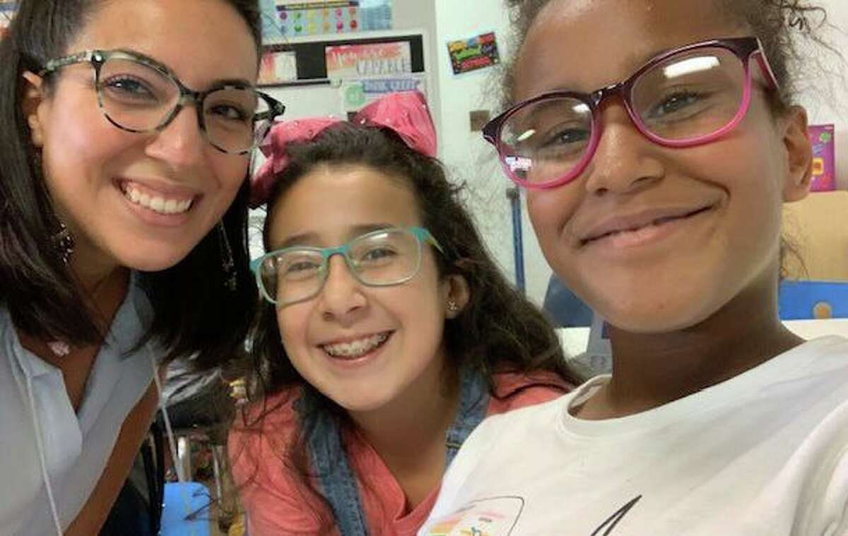 Carolina Ahumada, left, manager of the Family First in Education program run by Family Centers, with students in the program.