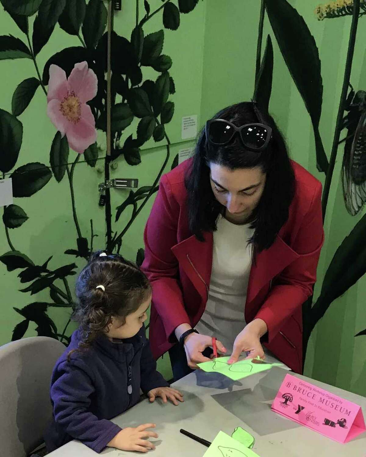 Carolina Ahumada of Family First in Education, a collaborative between Family Centers, the YMCA, and Greenwich Public Schools, helps Amber de la Puente cut out faces created during The Comic Tree Workshop at Bruce Museum.