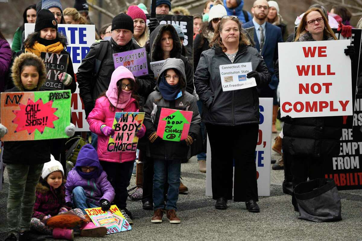Opponents to ending the religious exemption from the state's school vaccination requirements gather outside the State Capitol, Wednesday, Feb. 5, 2020, in Hartford, Conn.