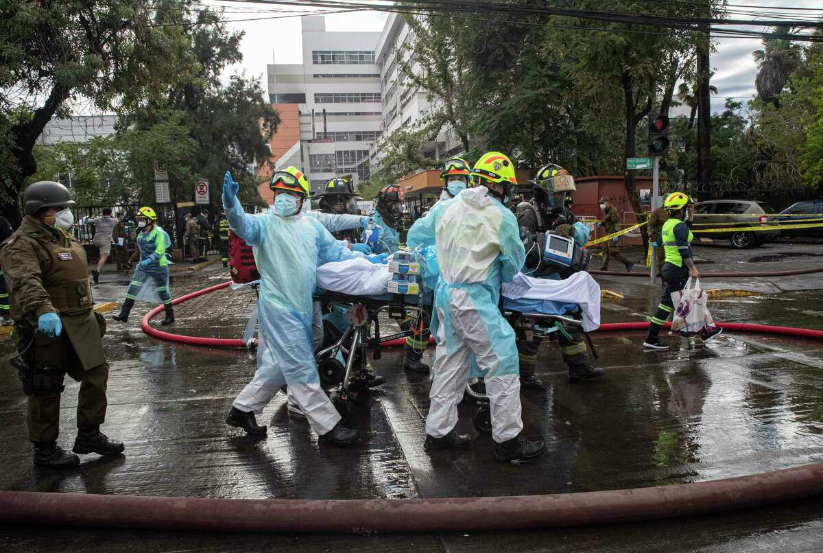 Health workers evacuate a COVID-19 patient from a fire inside a San Borja Arrarian hospital in Santiago, Chile, Saturday, Jan. 30, 2021.