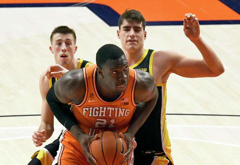 Illinois' Kofi Cockburn (front) powers to the basket as Iowa's Luka Garza (right) and Joe Wieskamp defend in the second half Friday night in Champaign. Photo: Associated Press