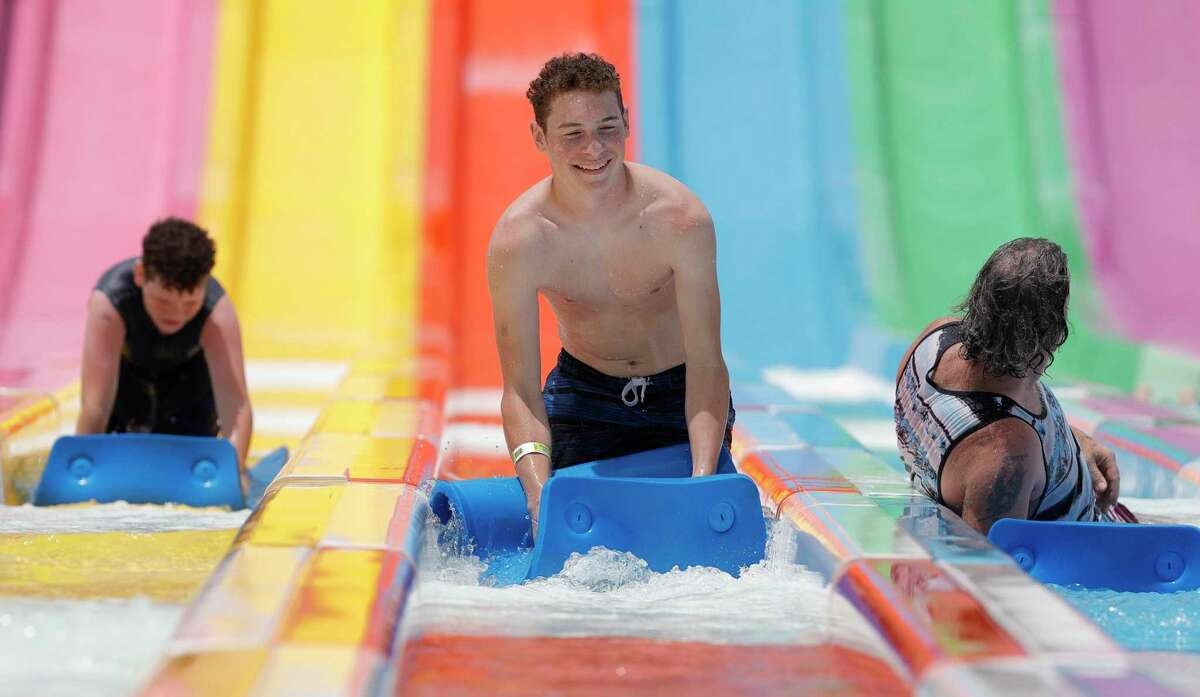 Benjamin Redus, center, shares a laugh after racing friends and family down a water slide at Big Rivers Waterpark, Saturday, May 23, 2020, in New Caney.