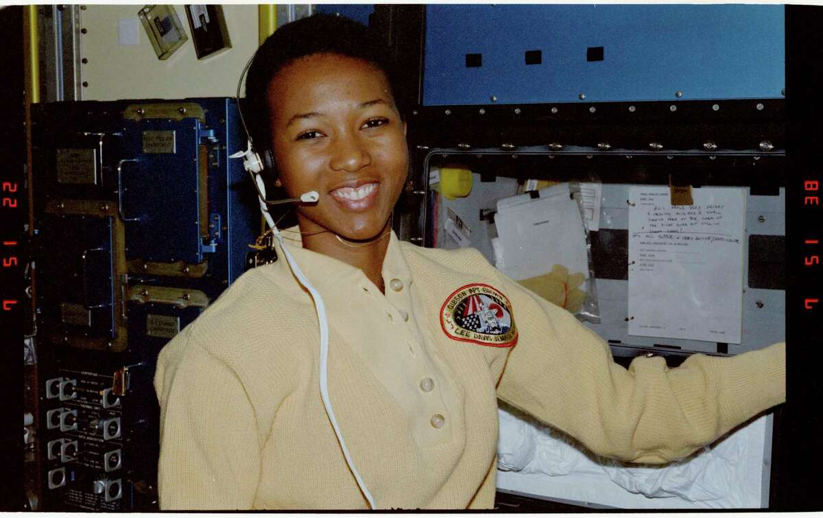 Mission Specialist Mae Jemison stands and smiles in front of general purpose workstation with head phones on, circa Nov. 30, 1998.(Courtesy photo/National Archives)