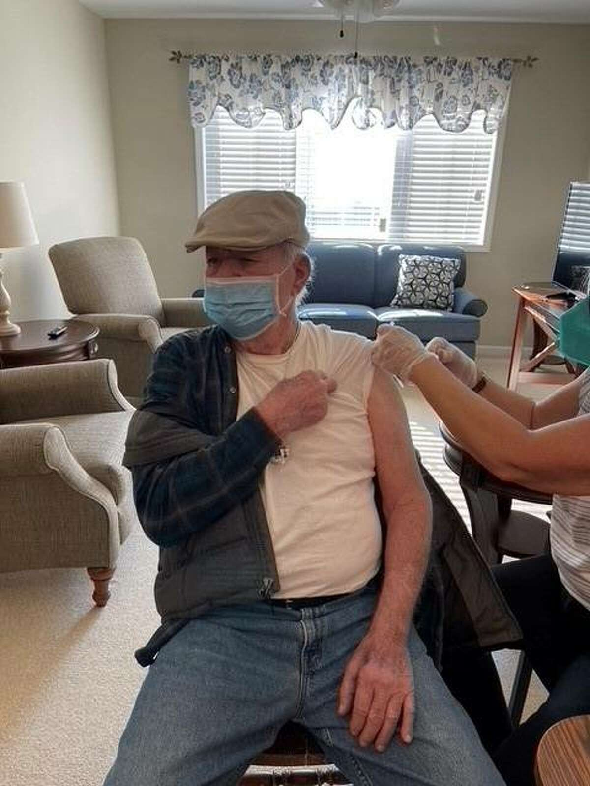 A resident of the Cedarhurst Senior Living in Bethalto on Friday receives his COVID-19 vaccination. Officials at the facility said most of the residents signed up for the vaccinations, which Cedarhurst built a disco-themed event around.