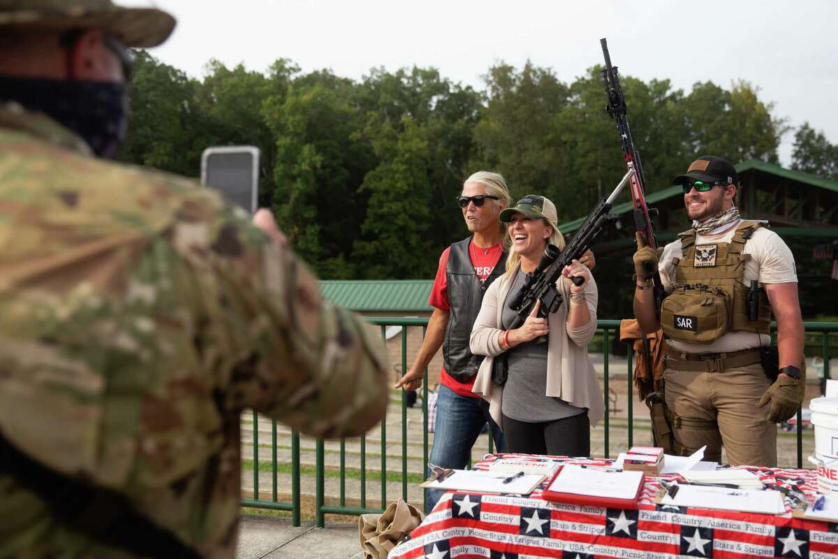 Marjorie Taylor Greene poses for a photo with Joe Webb, left and Jake Thomas, right, while holding a rifle at a campaign rally in Ringgold, Ga., on Sept. 19, 2020.