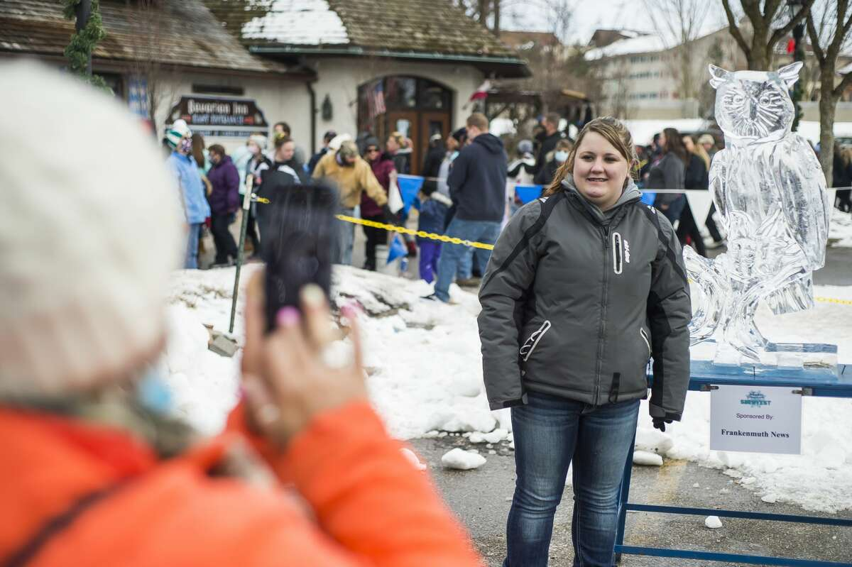 Tammy Heitkamp of Marion, left, takes a picture of Latasha Heitkamp, right, with an ice sculpture of an owl during the annual Zehnder's Snowfest Saturday, Jan. 30, 2021 in Frankenmuth. (Katy Kildee@mdn.net)