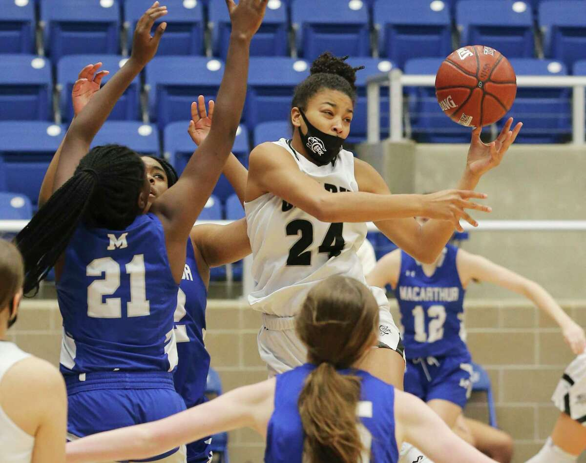 Clark's Aaliyah Roberson (24) contends for a rebound against MacArthur in girls basketball at Northside Sports Gym on Friday, Jan. 29, 2021. The Cougars defeated the Brahmas, 58-34, to advance to the next round.