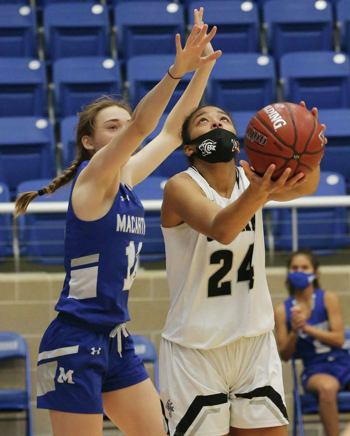 Clark's Aaliyah Roberson (24) looks to score against MacArthur's Nicole Wallace (12) in girls basketball at Northside Sports Gym on Friday, Jan. 29, 2021. The Cougars defeated the Brahmas, 58-34, to advance to the next round.