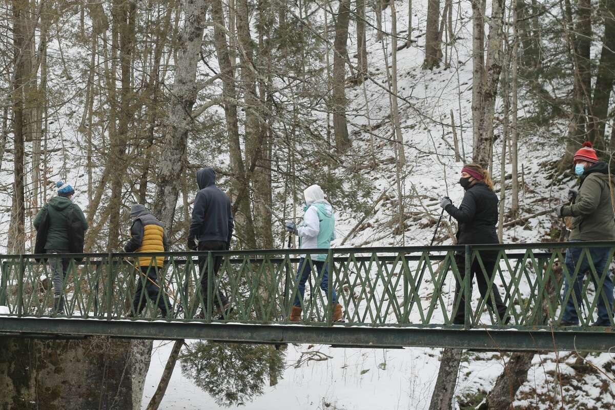 Spirit of the Woods Conservation Club member Devin Wegner leads hikers on a guided hike on the club property Saturday.
