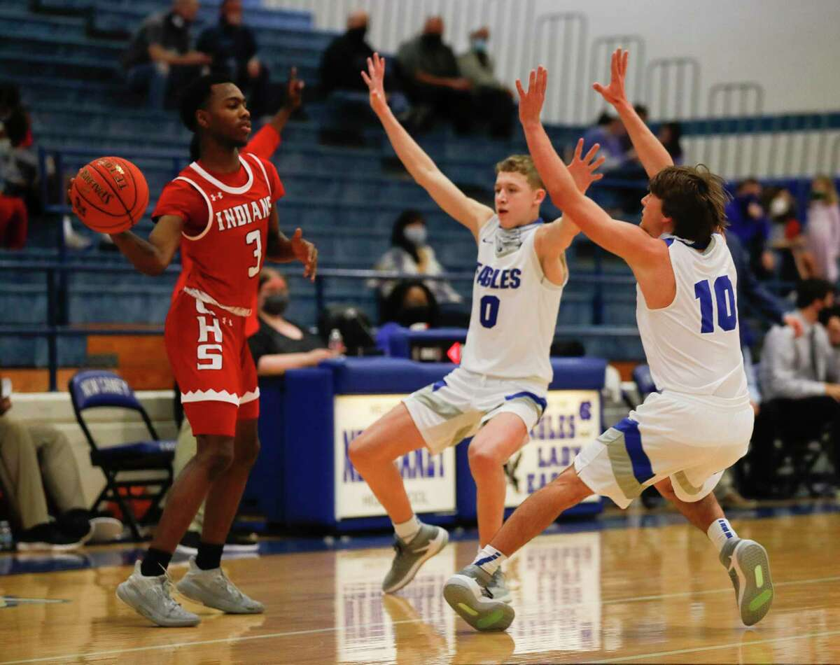 New Caney shooting guard Jaxon Olvera (0) and guard Ethan Brandon (10) pressure Cleveland guard Antonio Wheeler (3) during the first quarter of a District 20-5A high school basketball game at New Caney High School, Saturday, Jan. 30, 2021, in New Caney.