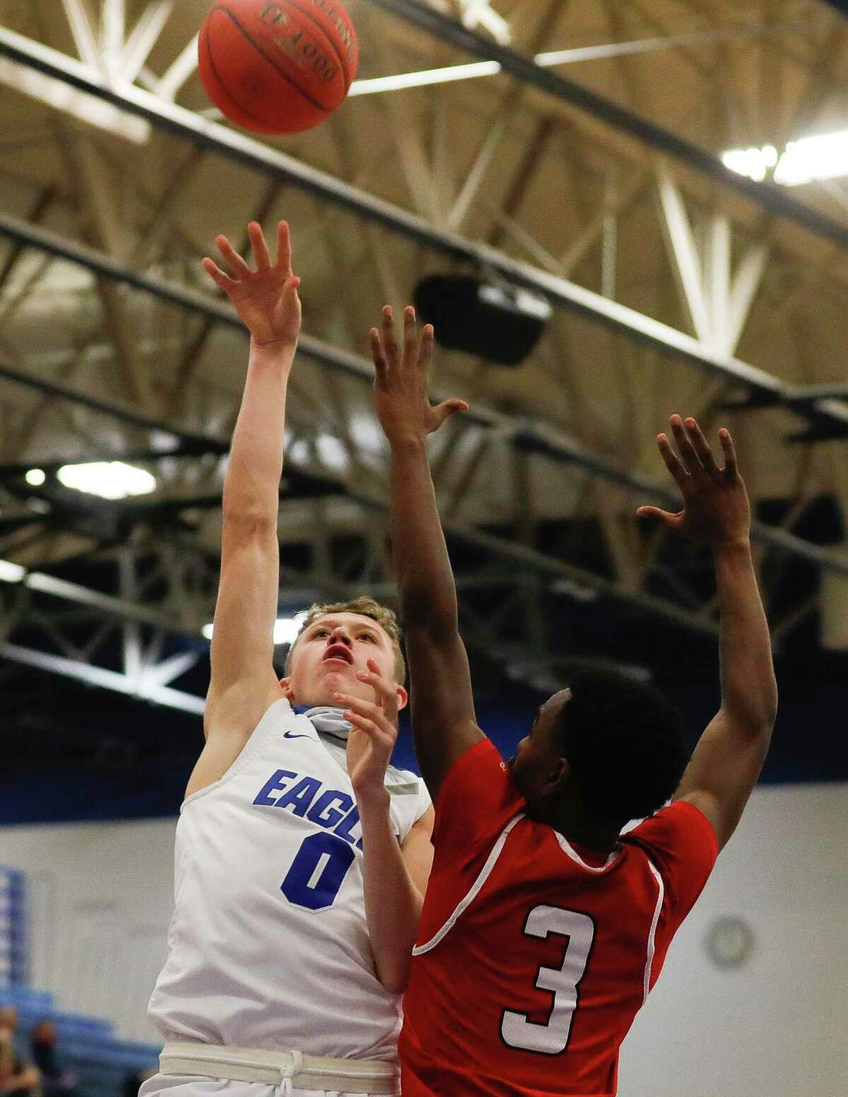 New Caney shooting guard Jaxon Olvera (0) shoots over Cleveland guard Antonio Wheeler (3) during the first quarter of a District 20-5A high school basketball game at New Caney High School, Saturday, Jan. 30, 2021, in New Caney.