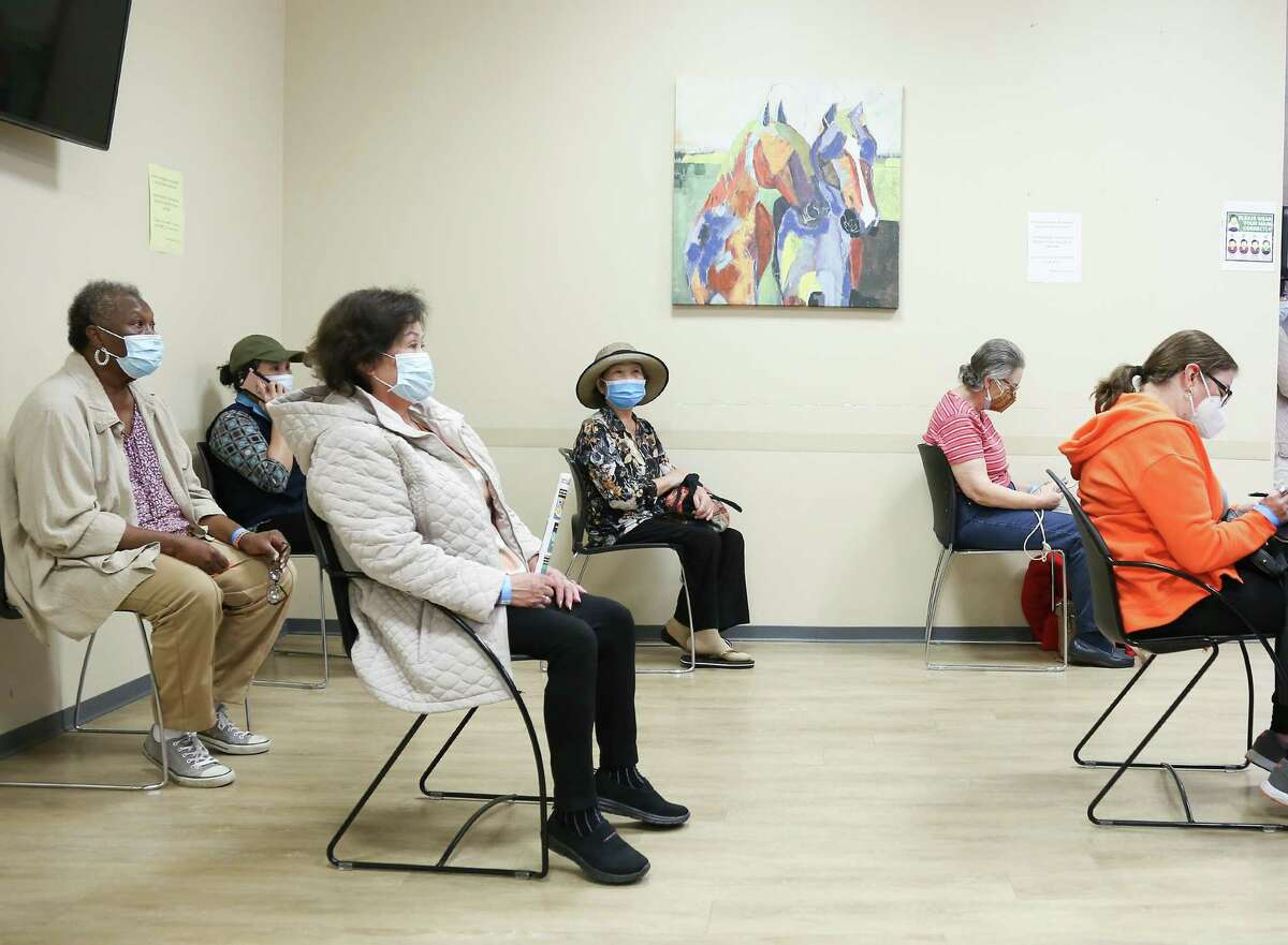 Recently vaccinated people wait for 15 minutes after getting the Moderna COVID-19 vaccine at HOPE Clinic in Houston on Saturday, Jan. 30, 2021.