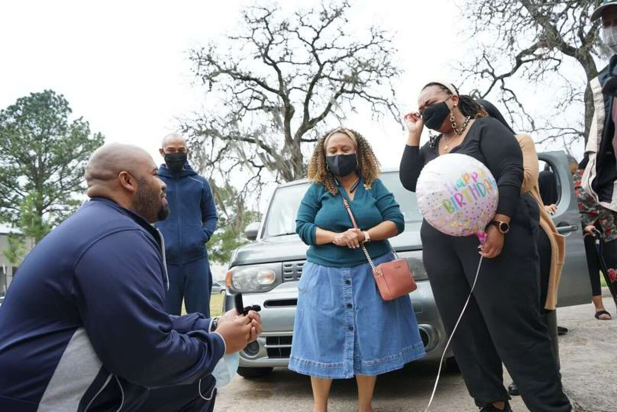 Jimmie Captain, left, proposes to his girlfriend, Ashley Turner, right holding balloon, Saturday, Jan. 30, 2020, in Houston. Turner is the daughter of Houston Mayor Sylvester Turner.