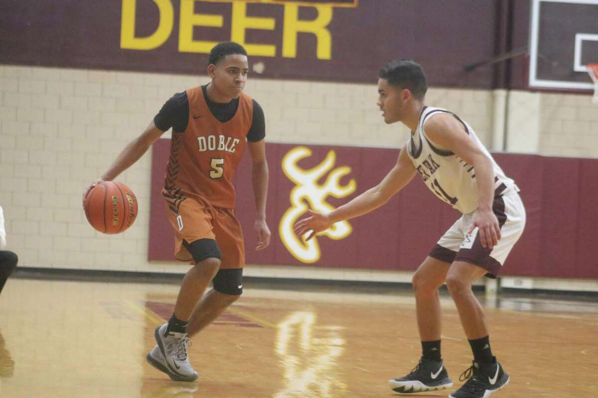 Deer Park's Michael Romero guards Waymon Hayes during Saturday's 22-6A game in Watkins Gym. Hayes and Co. officially began making plans for the state playoffs, following the 38-28 triumph.