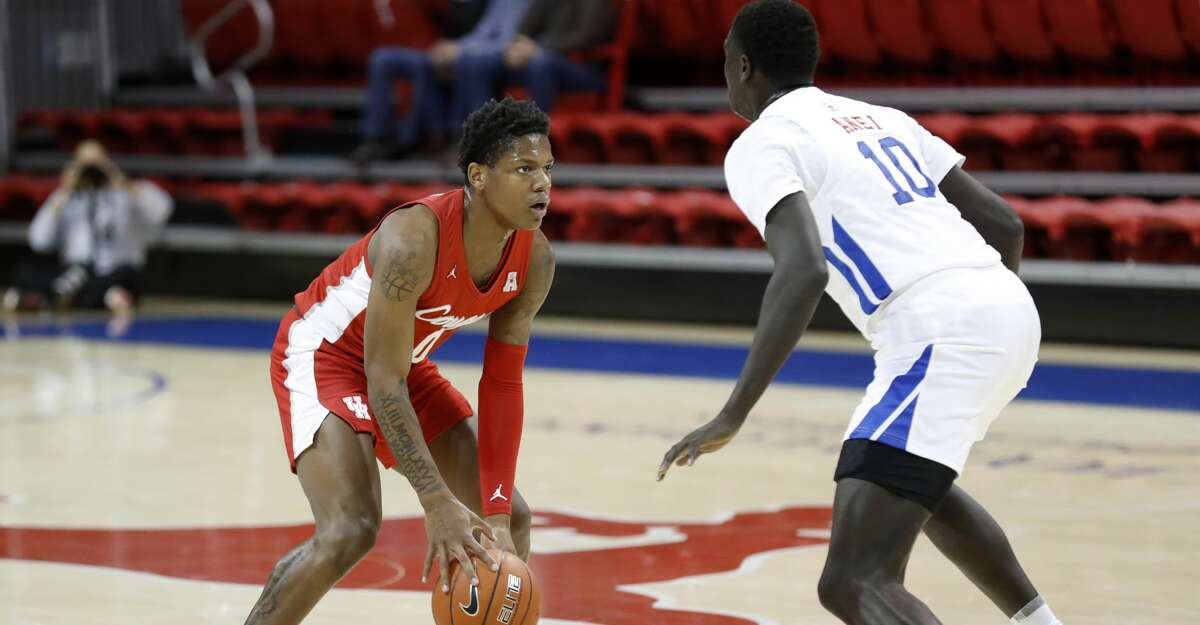 SMU forward Yor Anei (10) defends as Houston guard Marcus Sasser (0) dribbles during the first half of an NCAA college basketball game in Dallas, Sunday, Jan. 3, 2021. (AP Photo/Roger Steinman)