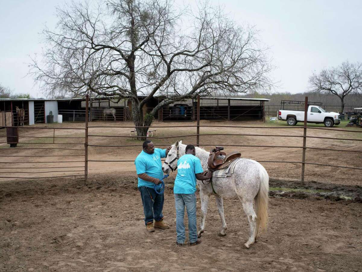 Gary Brown, left, of the Tone City Ryderz trailriding club on San Antonio's East Side, gets his cousin's horse Smoke ready to ride alongide his nephew Jo'vaughn Wolford, 16, on Saturday, January 23, 2021, in a rural part of east Bexar County. Brown has been riding horses since he was 10.
