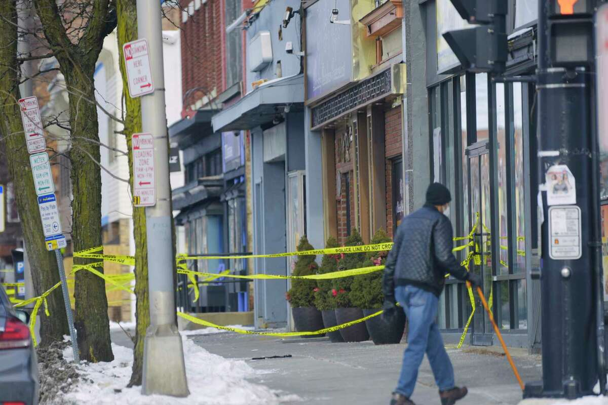 Police tape blocks off a section of the sidewalk at the scene near 211 Central Ave. in Albany, N.Y., where Albany Police said that three women and two men were shot late Saturday night. One woman died. (Paul Buckowski/Times Union)