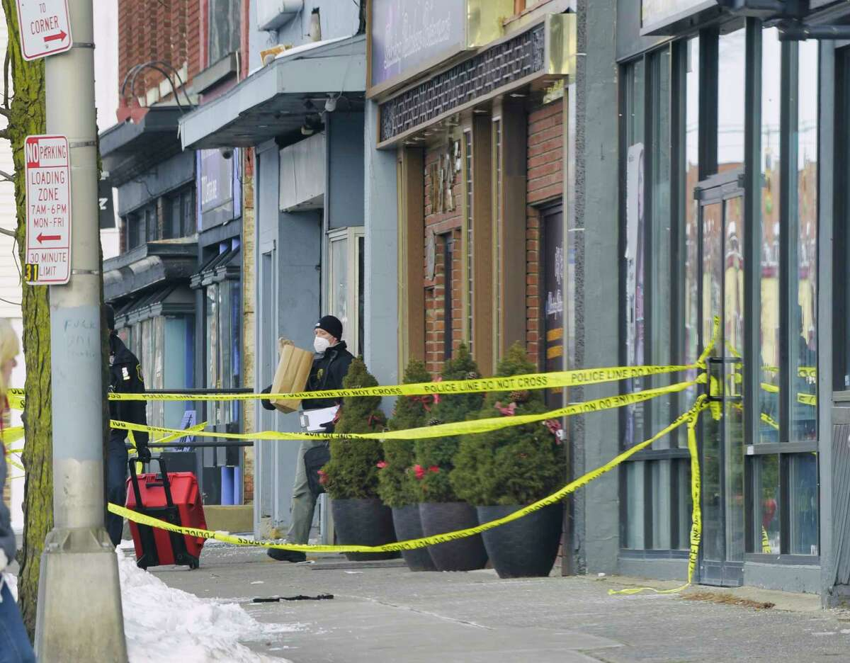 Police tape blocks off a section of the sidewalk at the scene near 211 Central Ave. as investigators leave the scene on Sunday, Jan. 31, 2021, in Albany, N.Y. Albany Police said that three women and two men were shot late Saturday night, one woman died. (Paul Buckowski/Times Union)