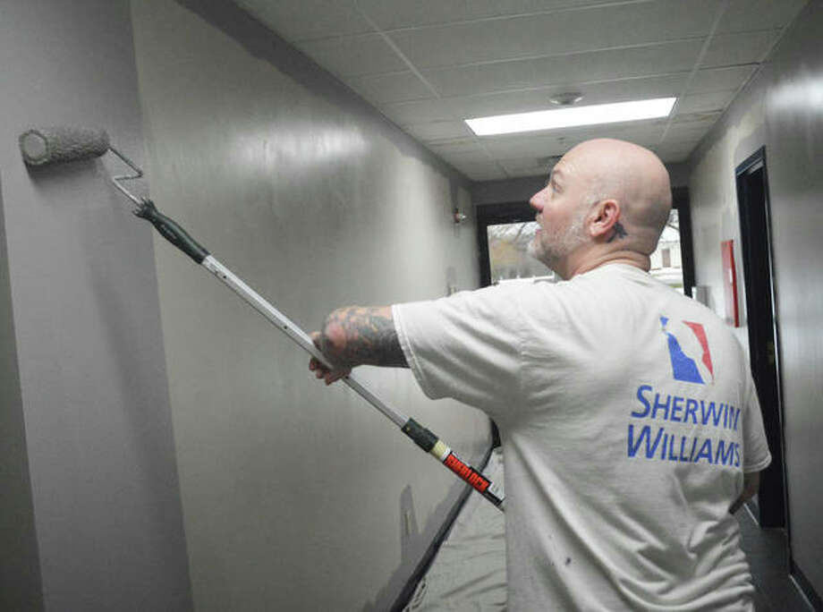 Travis Gillig of Signature Custom Painting in Edwardsville was among four professional painters who donated their time on Saturday morning to paint the lounge and entrance hall at Edwardsville American Legion Post 199. Photo: Scott Marion | The Intelligencer