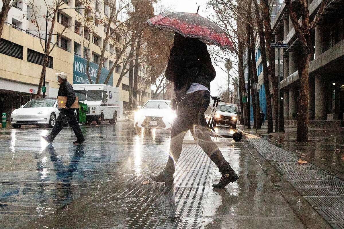 People cross a rainy South Third Street in San Jose, Calif. Windy, light rains again are forecast for the Bay Area.