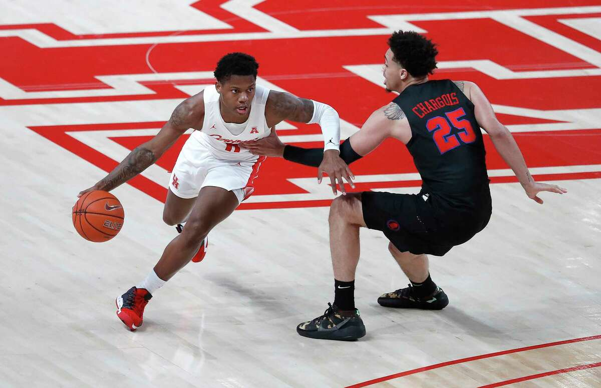 Houston Cougars guard Marcus Sasser (0) drives around Southern Methodist Mustangs forward Ethan Chargois (25) during the first half of an NCAA men's basketball game at the Fertitta Center, in Houston, Sunday, Jan. 31, 2021.