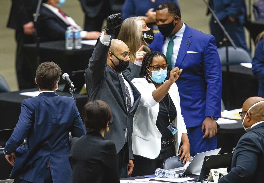 State Rep. Justin Slaughter, D-Chicago, holds up his fist while wearing a black glove after a criminal justice reform bill passed during the lame-duck session for the House of Representatives. Photo: Justin L. Fowler | AP / 2021 The State Journal-Register