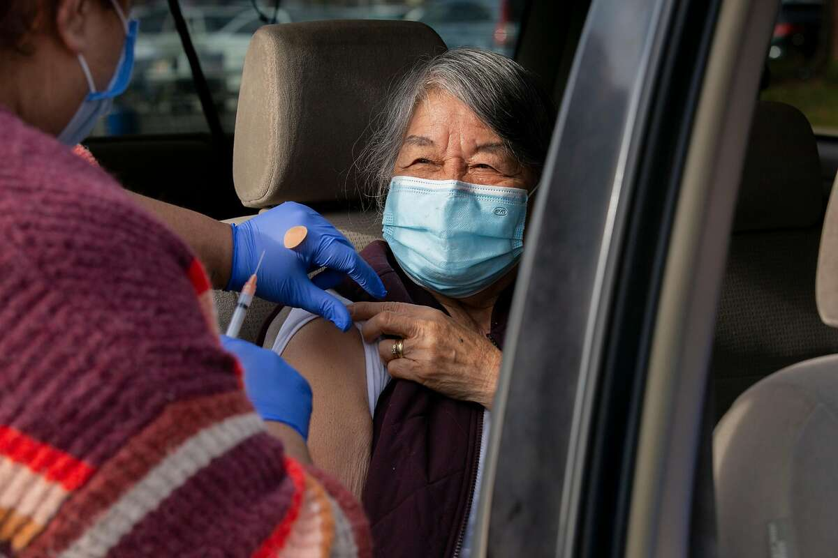 Medical assistant Rajinder Kaur vaccinates Wilhelmina Ismael at a drive-through station at Bay Area Community Health in Fremont.