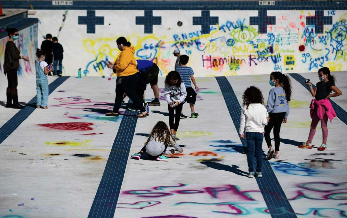 Families spray paint inside the Evelyn Rubenstein JCC outdoor pool, Sunday, Jan. 31, 2021, in Houston. The Jewish Community Center invited 15 families to join the groundbreaking celebration events ahead of the new facilities. The first phase of the project will be to renovate the fitness facilities including the pool.