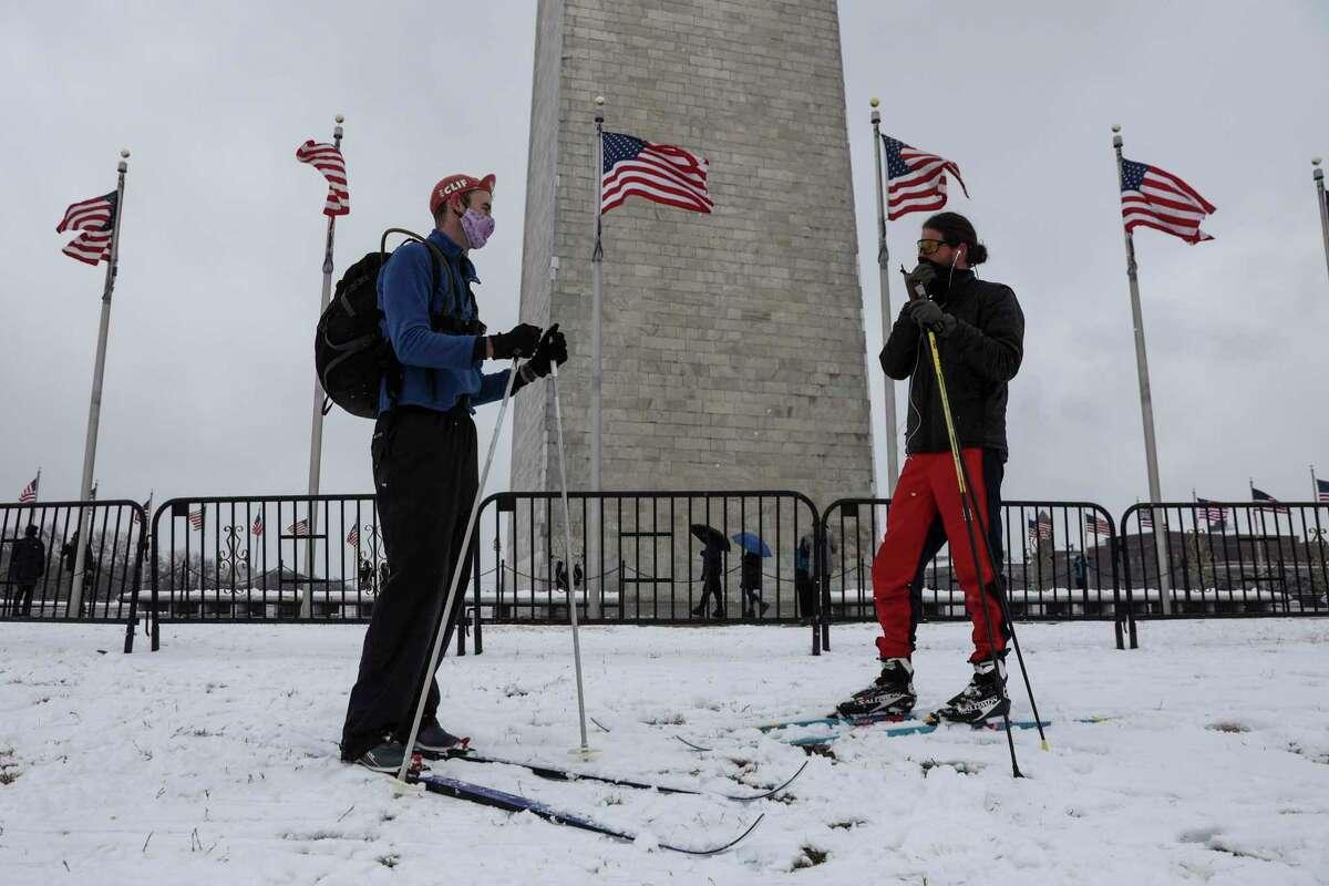 Travis Fondow, right, and a friend, prepare to ski near the Washington Monument in Washington on Sunday, Jan. 31, 2021.