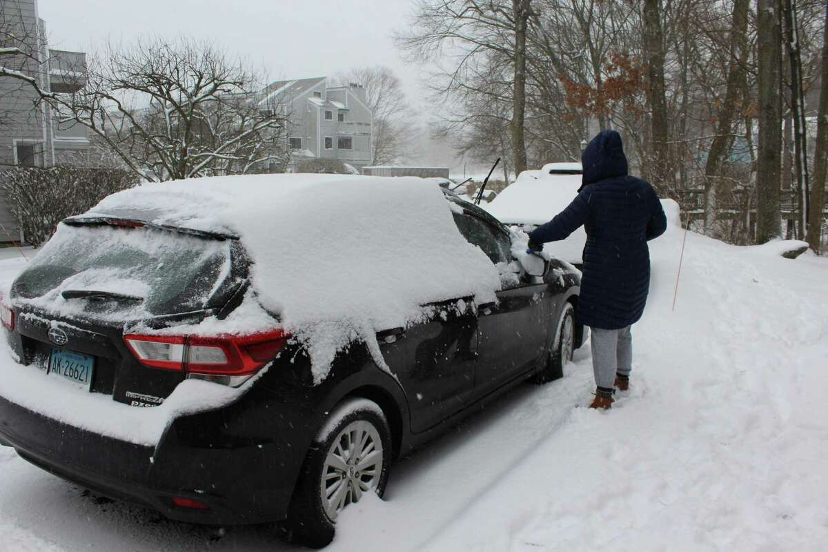 A Norwalk resident cleans off their car during a snow storm Monday, Feb. 1, 2021.
