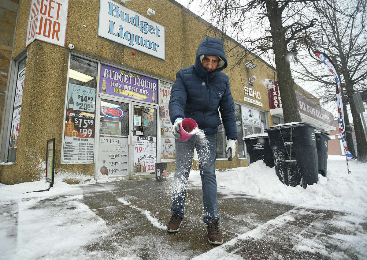 Store manager Tehseen Hussain, salts the sidewalk outside Budget Liquor during the blizzard on West Avenue in Norwalk, Conn. on Monday, February 1, 2021. In Norwalk, all students are equipped with the technology needed for remote learning, but the district may still call a snow day if a storm may bring power or internet outages.