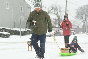 Stokes and Britton Carrigan, and their children Stokes, 6, and Elle, 1, don't let the snow prevent their morning walk for coffee and breakfast on Cove Avenue in Norwalk, Conn. on Monday, February 1, 2021.