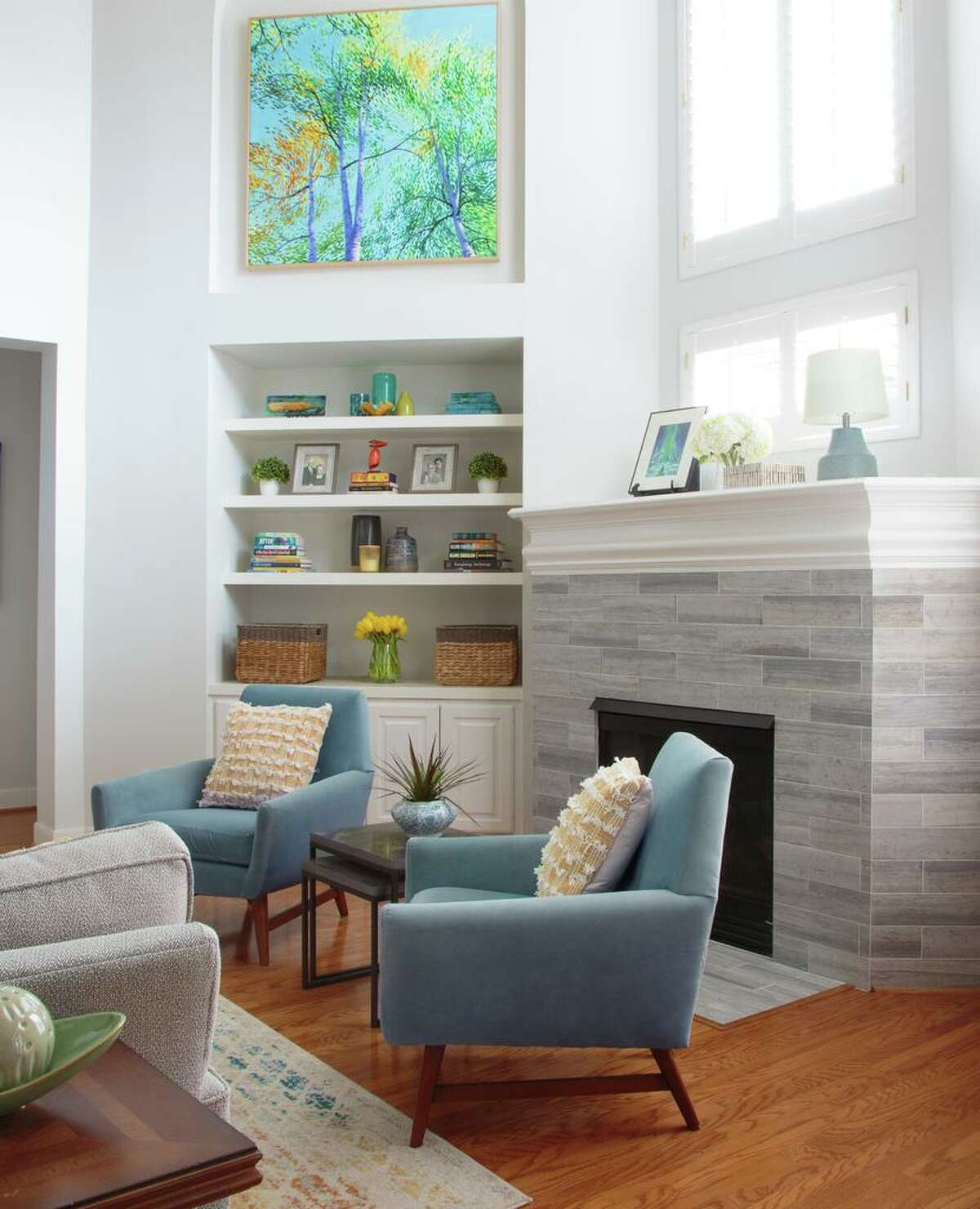 Now, the fireplace has gray-white tile and built-in cabinets that once held a TV are now display shelves.