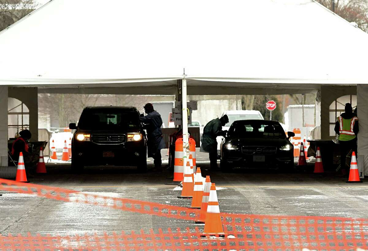 Health care workers administer COVID-19 swab tests at the drive through testing site at University at Albany Monday, Feb. 1, 2021 in Albany, N.Y. (Lori Van Buren/Times Union)