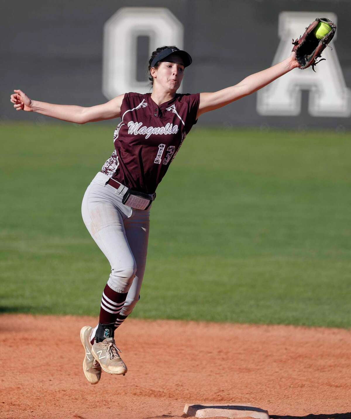 Magnolia shortstop Gabrielle Huetter (13) catches a high throw to second base during the third inning of a non-district high school softball game at Oak Ridge High School, Thursday, Feb. 27, 2020, in Oak Ridge.