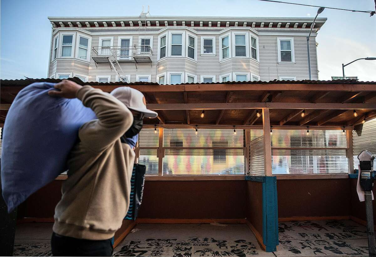 A pedestrian walks by the empty outdoor dining setup at Yasmin restaurant in the Mission District where COVID-19 restrictions had shut down businesses for most of December and January.