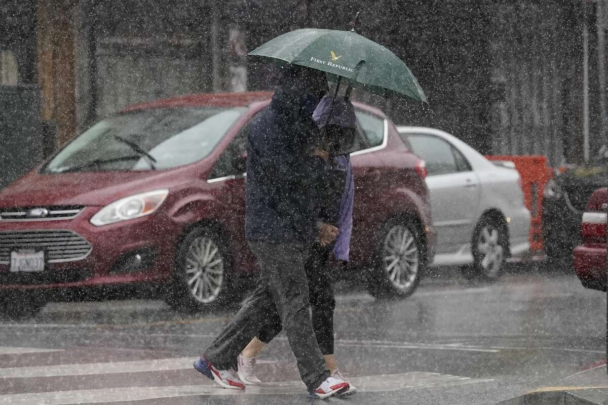 People carry an umbrella while walking in the rain in San Francisco, Sunday, Dec. 13, 2020.