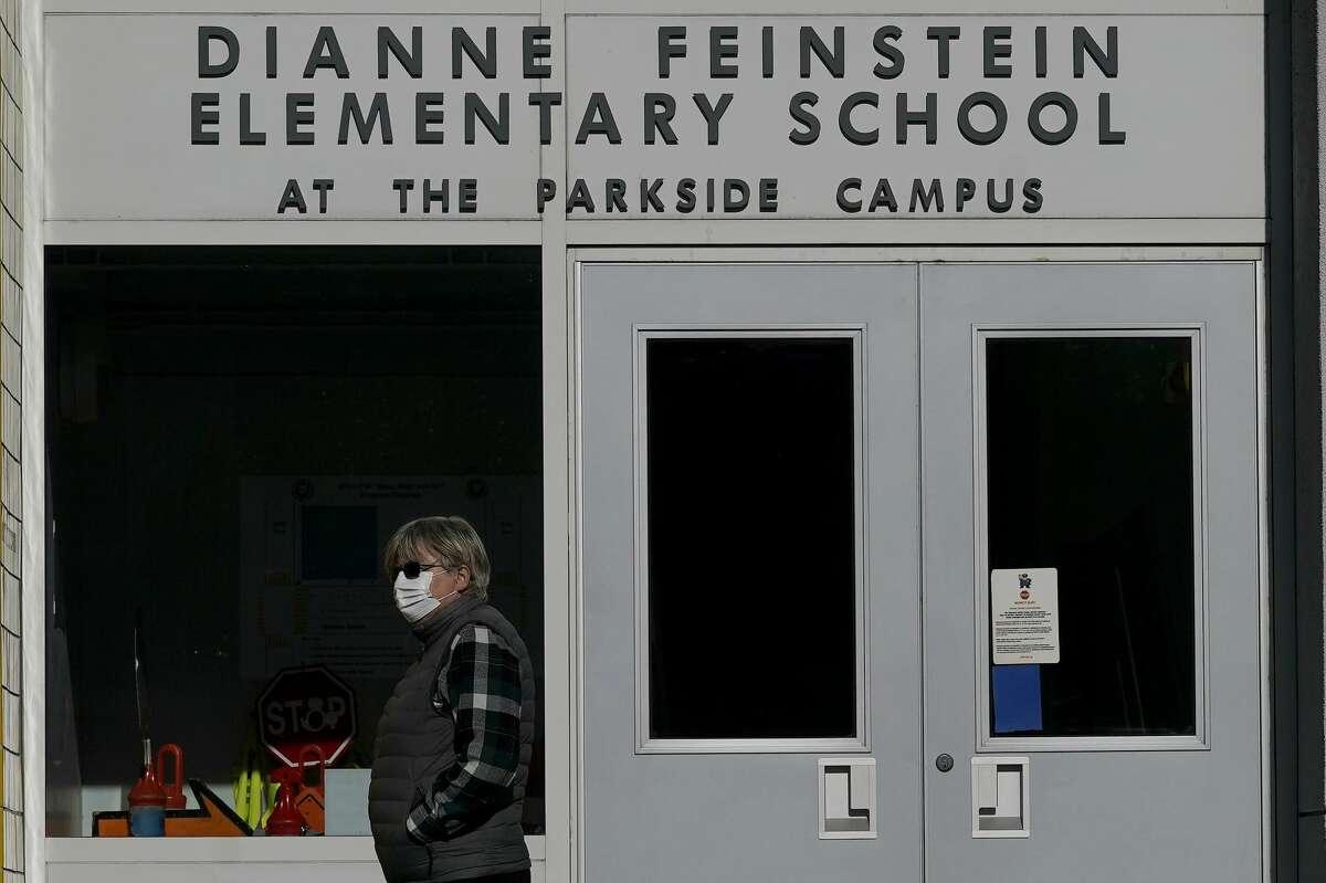 A pedestrian walks below a sign for Dianne Feinstein Elementary School in San Francisco.