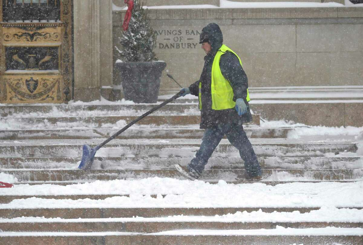 Fernando Barzoza clears snow from the steps of the Savings Bank of Danbury building on Main Street Monday morning. February 1, 2021, in Danbury, Conn.