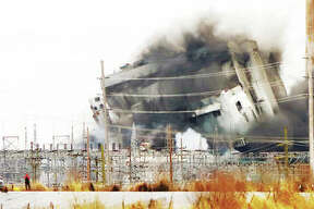 The former Wood River Power Station gently rolls over Monday morning after explosives blew out the lowest level steel girders holding the building up. The controlled blast dropped the building where workers quickly began tearing the steel apart. Illinois 3 was closed to traffic as a precaution. Although Monday's demolition plans initially called for dropping three smokestacks at the site, that work is being delayed to allow more time to inform the public about possible dust hazards associated with the work. A gallery of Monday's demolition is online at thetelegraph.com.