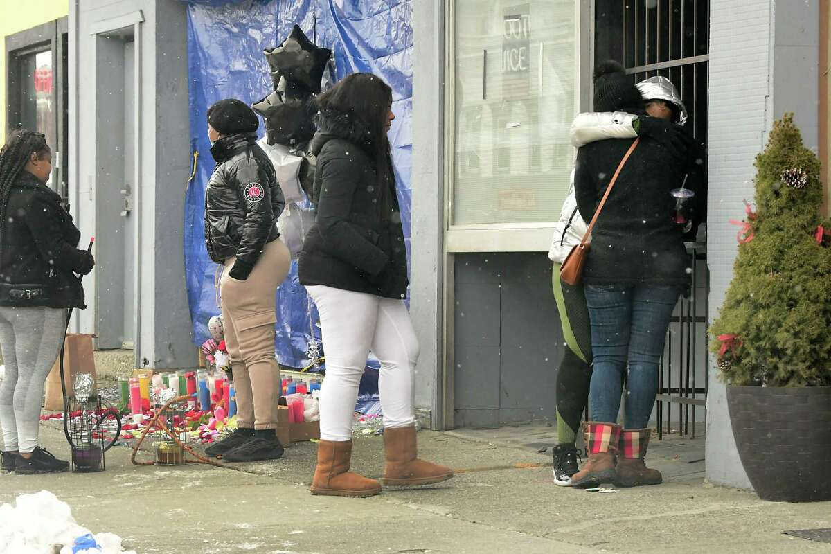 Women are seen gathered around a memorial in front of 211 Central Ave. on Monday, Feb. 1, 2021 in Albany, N.Y. Shanita Thomas, 32, died and four other people were injured when someone opened fired late Saturday at crowd gathered on Central Avenue. (Lori Van Buren/Times Union)