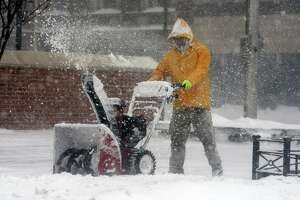 A man uses a snow blower to clear sidewalks along Main St. in Bridgeport, Conn. Feb. 1, 2021.