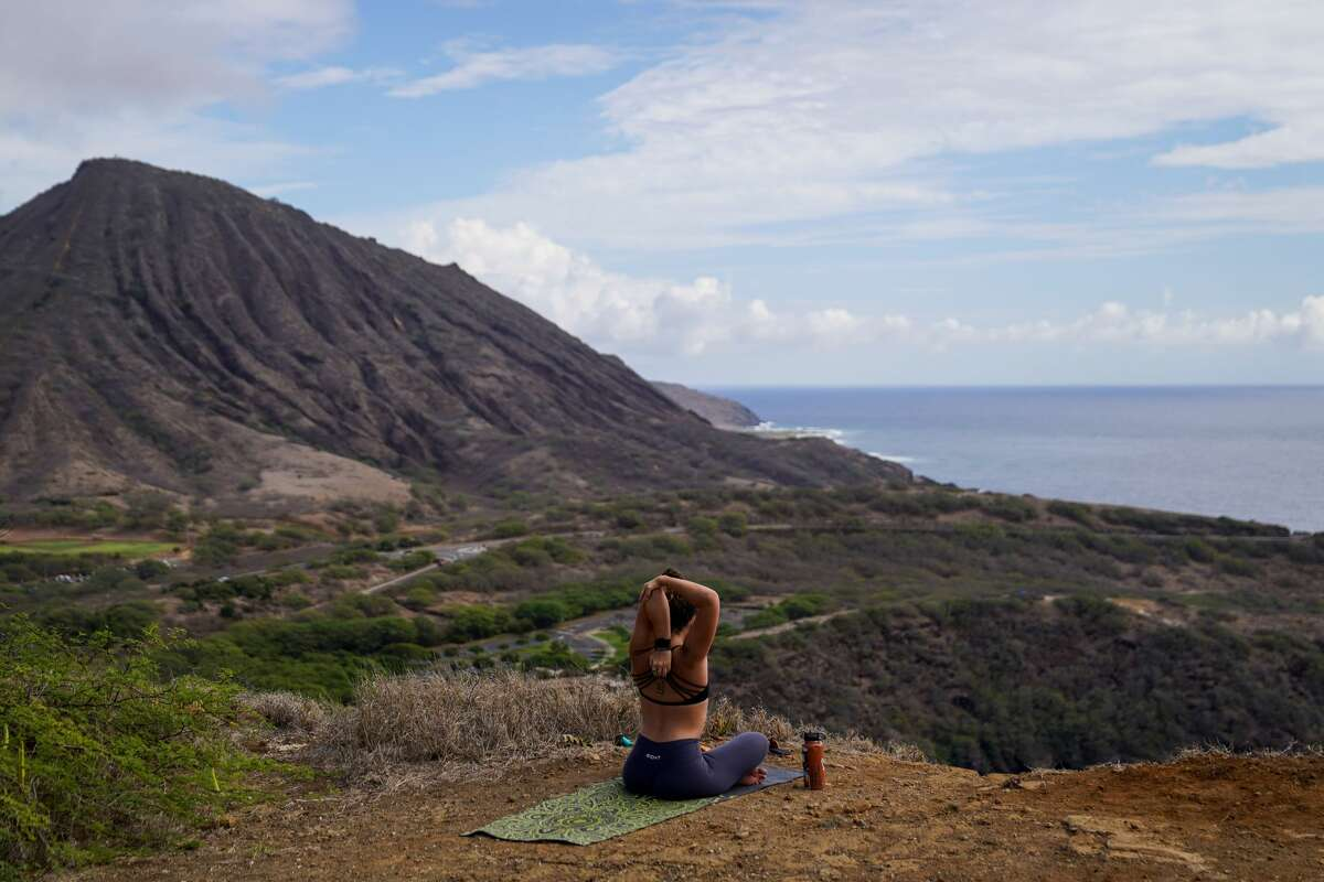 From a hiking trail overlooking Hanauma Bay, Jessica Linster, 24, of Kahala, stretches after morning yoga on Oct. 18, 2020, in Hawaii.