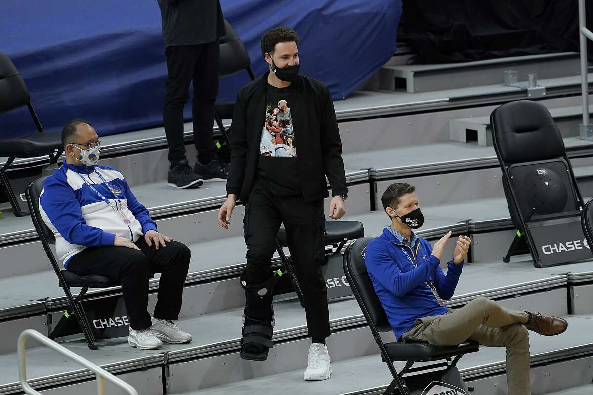 Injured Golden State Warriors guard Klay Thompson, center, watches during an NBA basketball game between the Warriors and the Detroit Pistons in San Francisco, Saturday, Jan. 30, 2021. (AP Photo/Jeff Chiu)