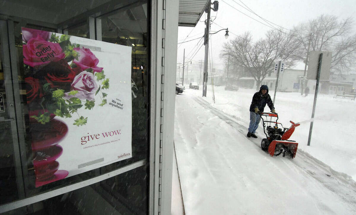Richard Hall, owner of Danker Florist, moves snow on Feb. 14, 2007, from the front of his store on Central Avenue in Albany, New York. (Skip Dickstein / Times Union)