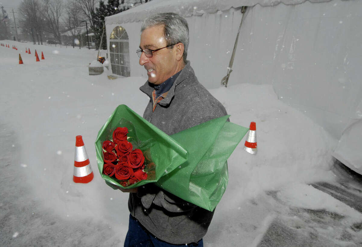 Lou Manico carries two dozen roses from the Colonie Volunteer Fire Company's fundraising effort on Feb. 14, 2007, at the fire house in Colonie, New York. Manico braved the fierce storm to get roses for his wife on Valentine's Day. (Skip Dickstein / Times Union)