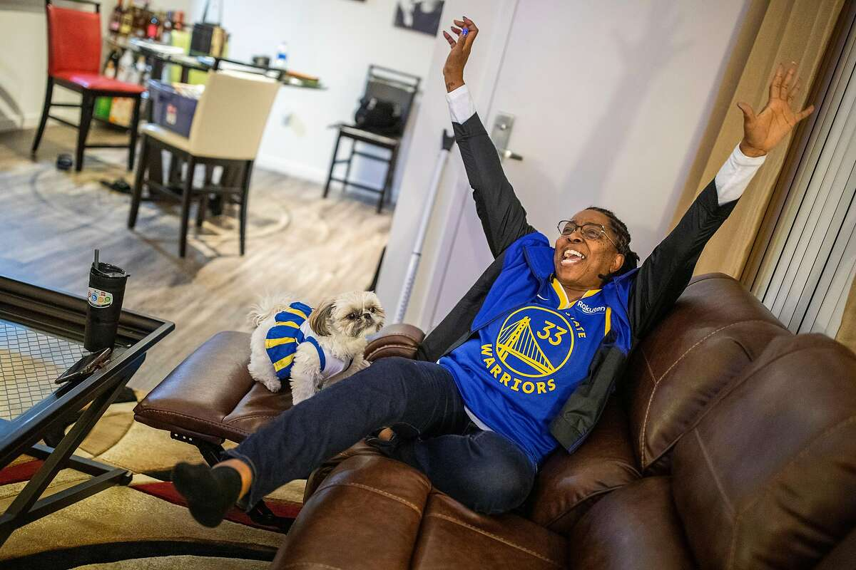 Donzaleigh Artis, watching the NBA game with her dog Celerie at her new San Francisco apartment, reacts as her son and Golden State Warriors center James Wiseman dunks against the Los Angeles Lakers in the first quarter on Monday, Jan. 18, 2021.